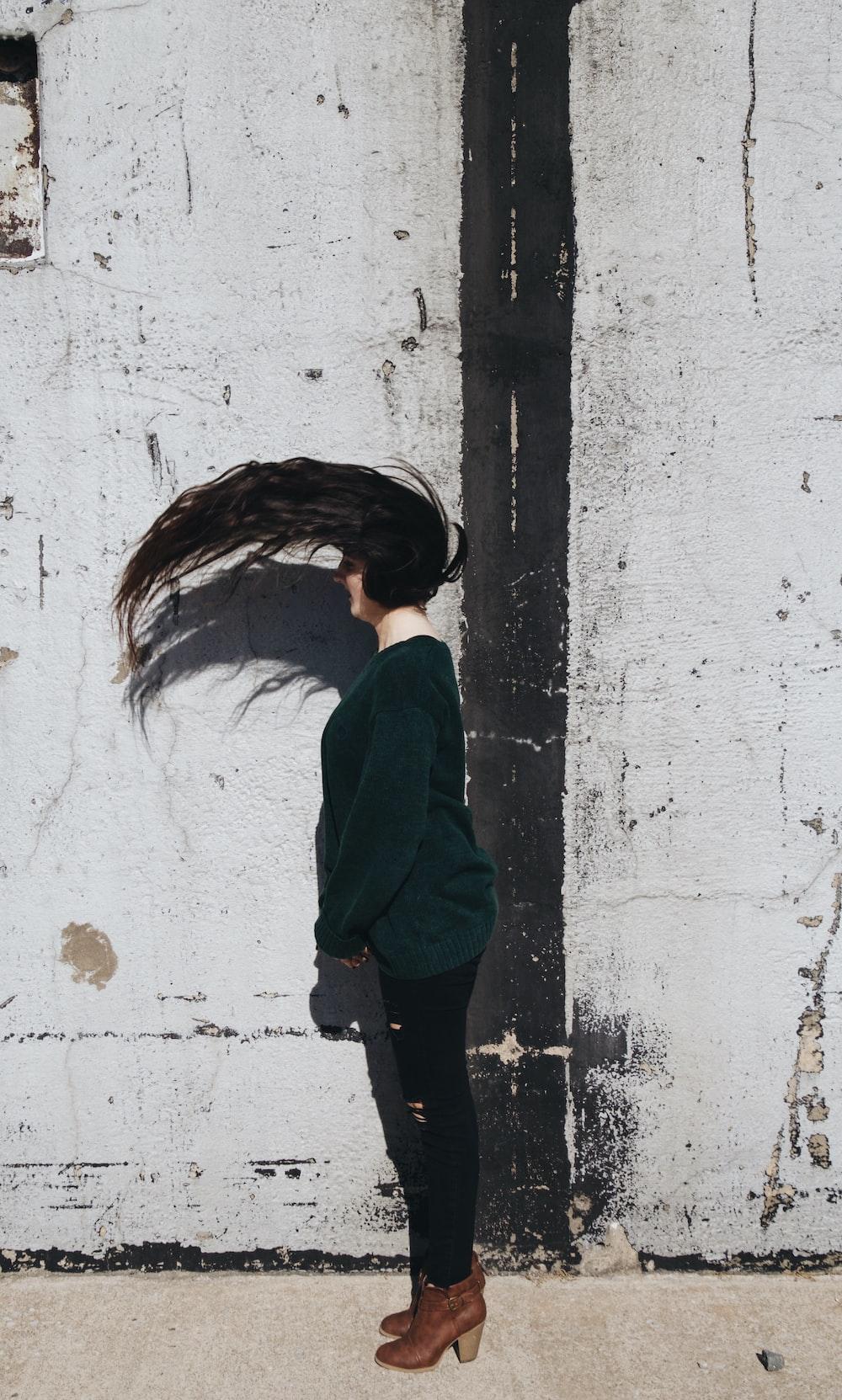 woman wearing green long-sleeved shirt standing beside white wall