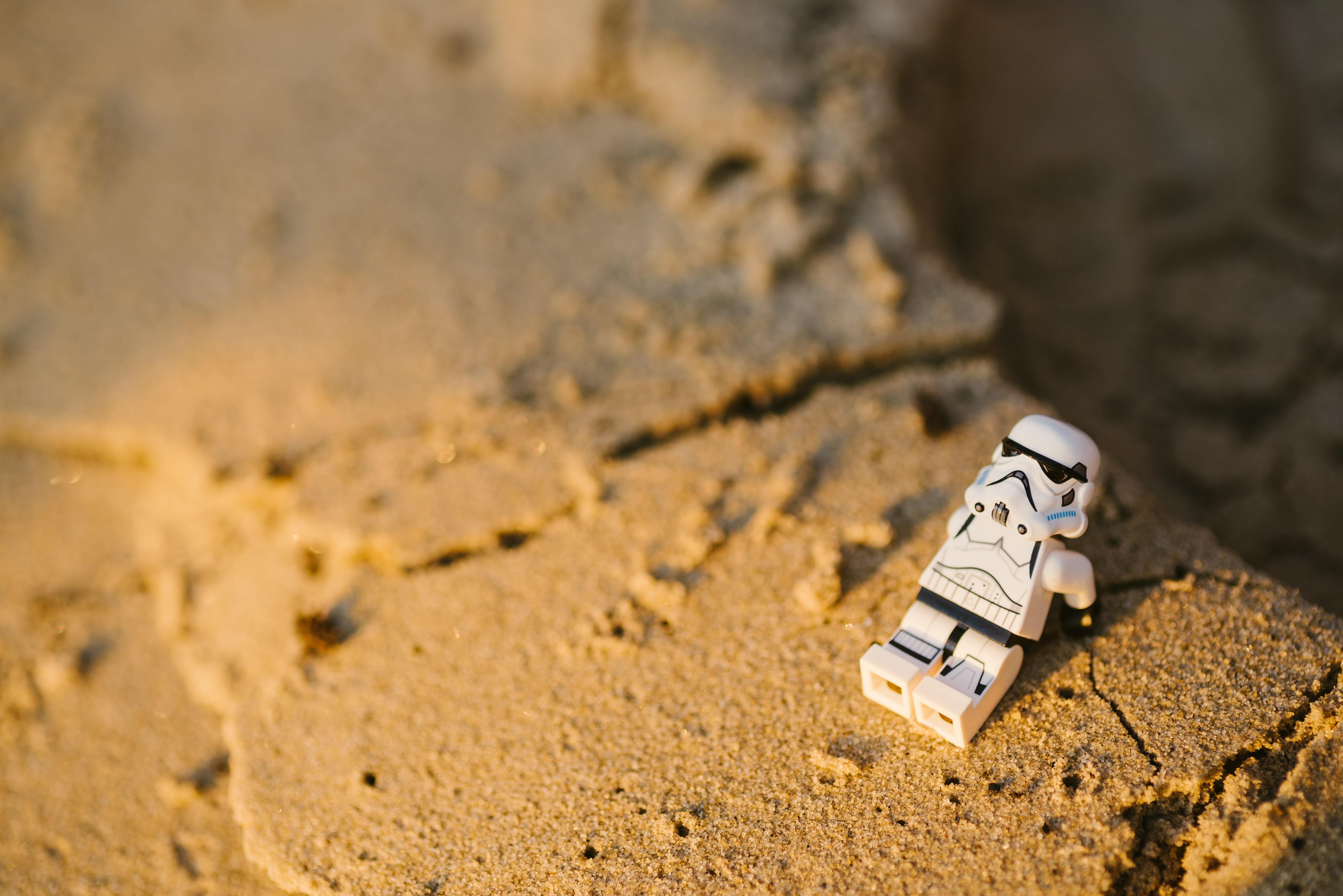 selective focus photography of Star Wars Stormtropper minifigure on sand