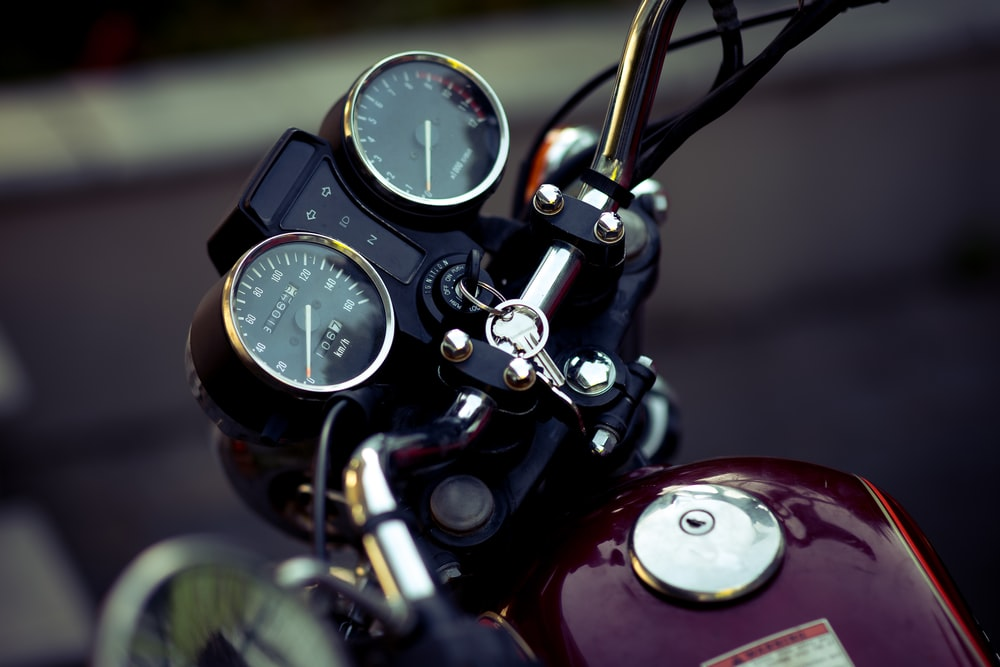 selective focus photography of motorcycle speedometer