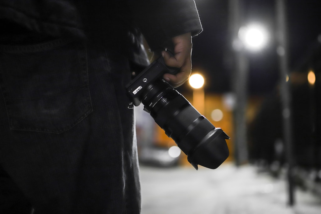 standing person holding DSLR camera during night