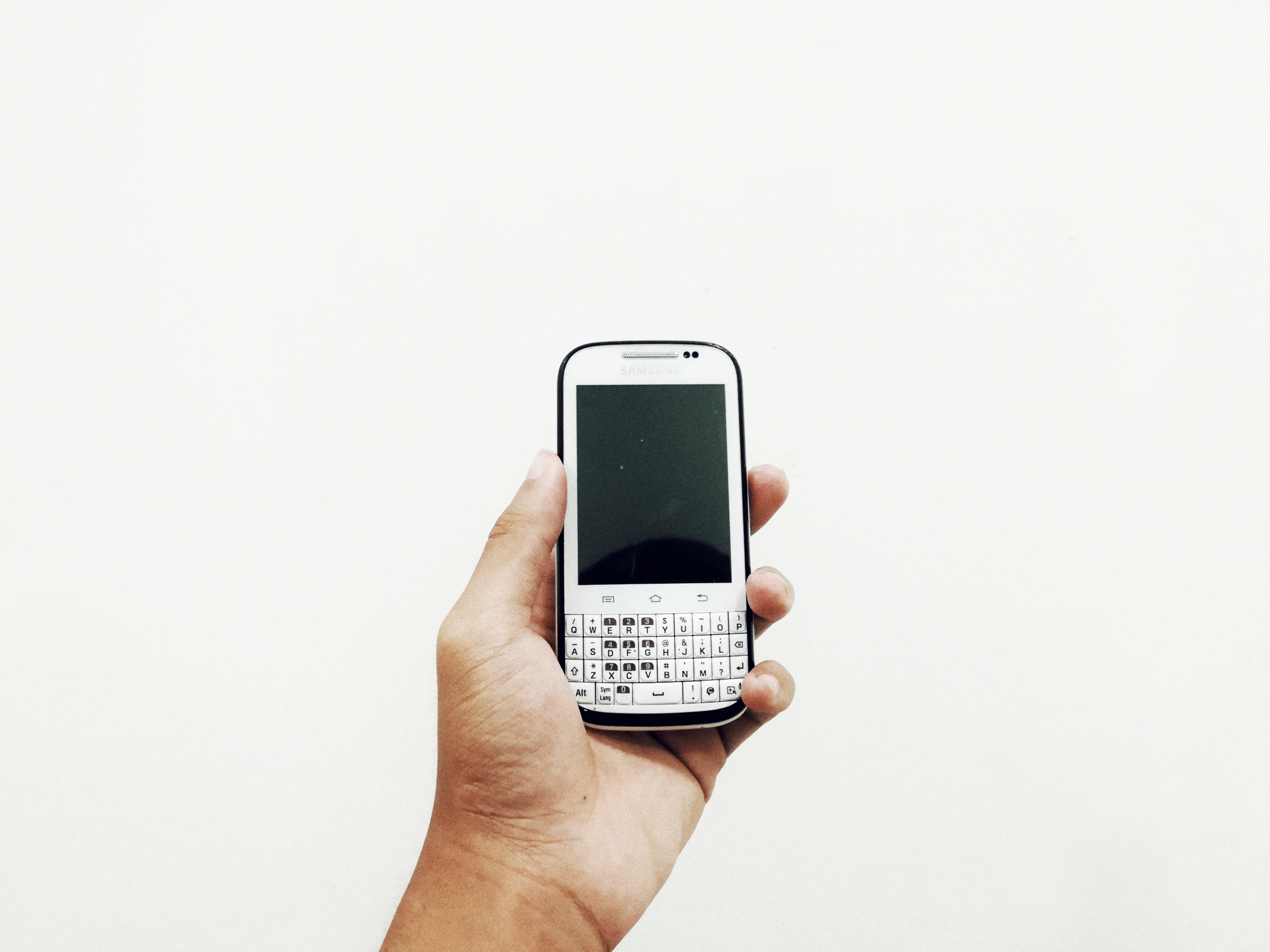 person holding white QWERTY phone