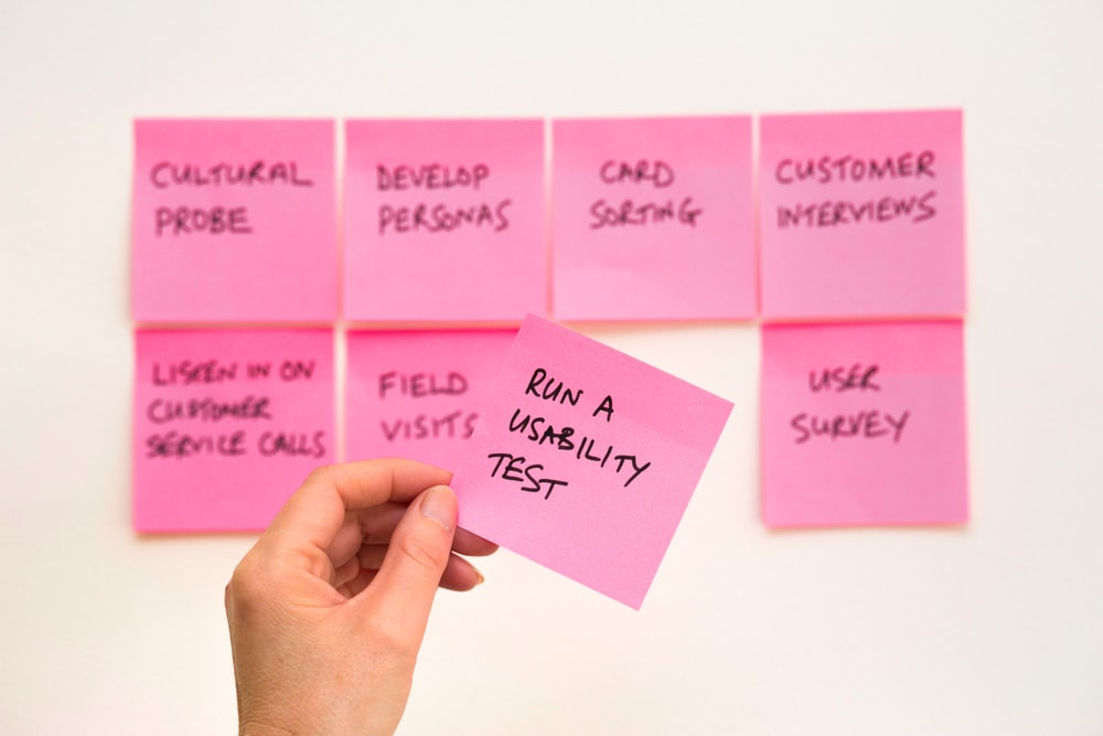 person holding pink sticky note