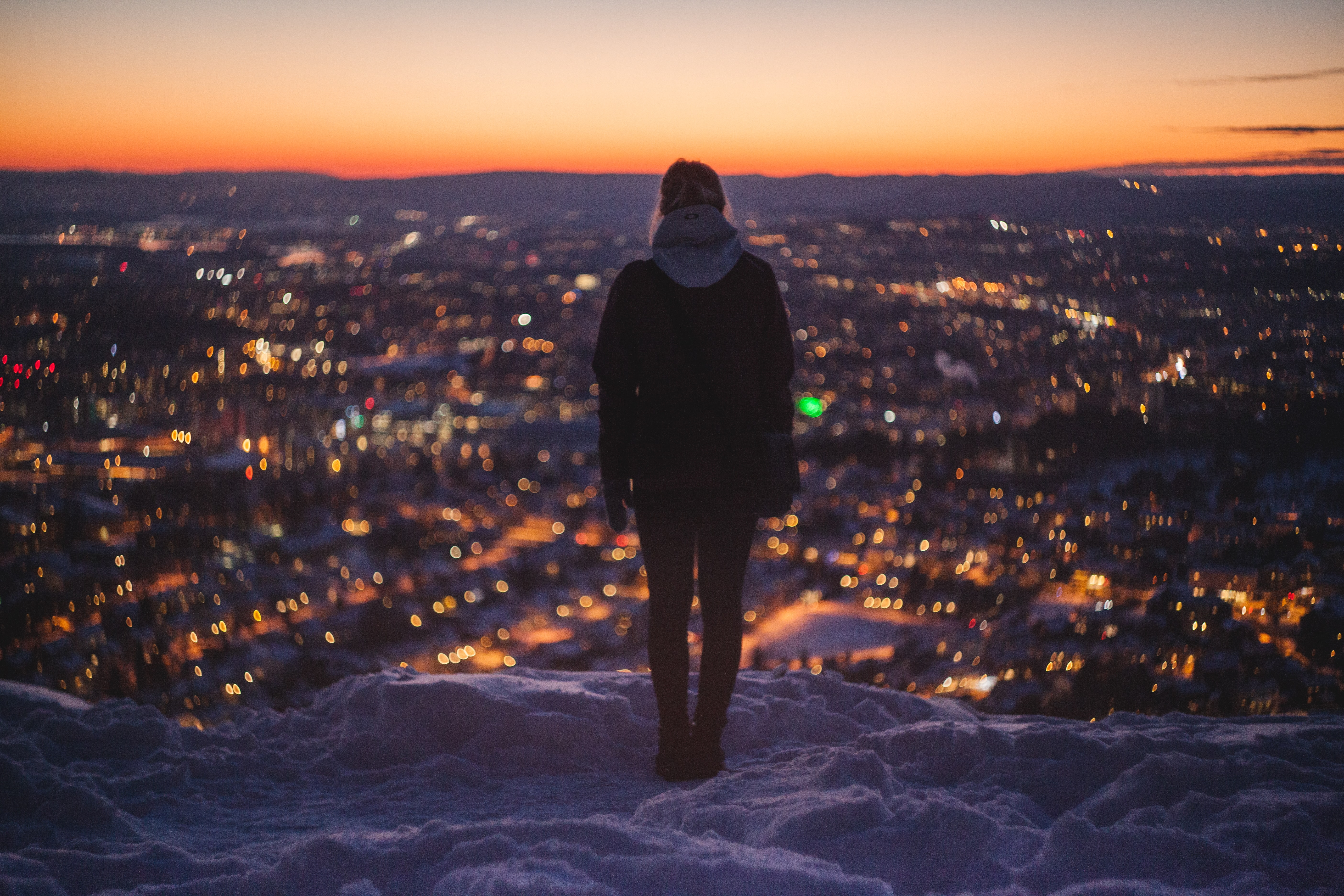 person standing on mountain looking on lights