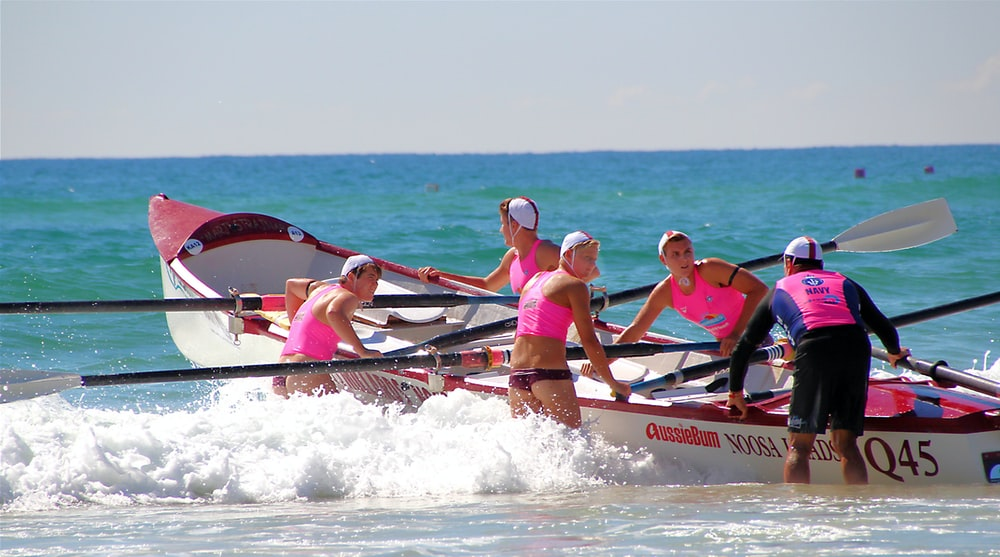 five women wearing pink crop tops about to ride on boat