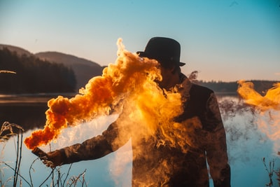 man holding flare smoke grenade teams background