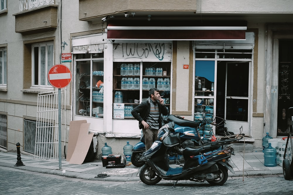 man standing near black and blue motor scooter on road