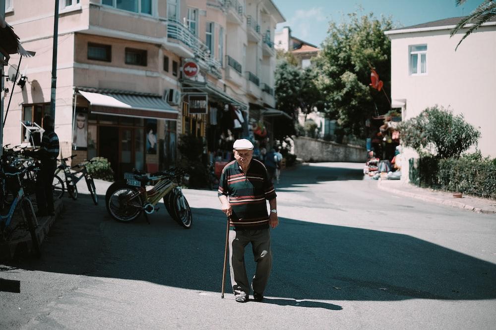 man walking while holding stick during daytime