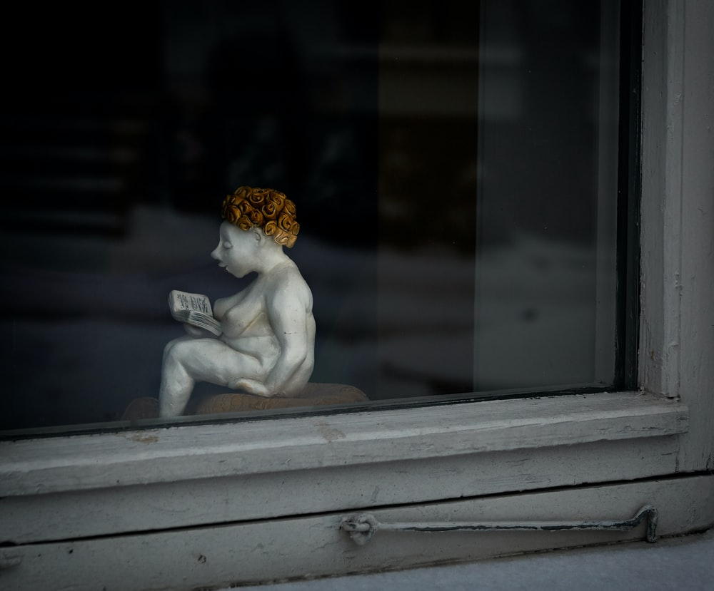 woman reading book figurine by the window