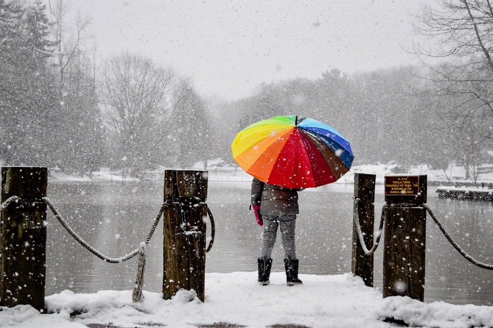 person holding multicolored umbrella standing on dock near lake