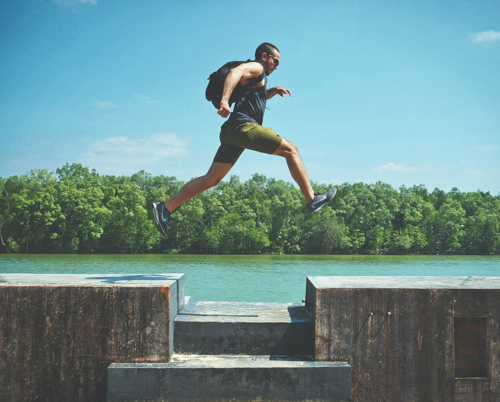 man leaping on concrete surface near body of water and forest at the distance during day