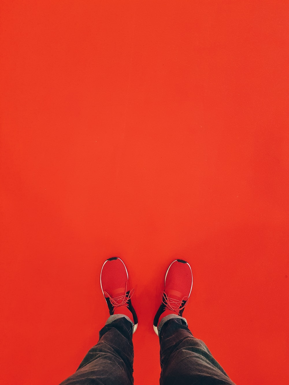 person wearing red running shoe