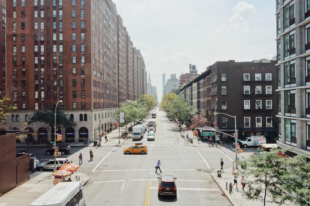 people walking on road beside cars between high rise buildings