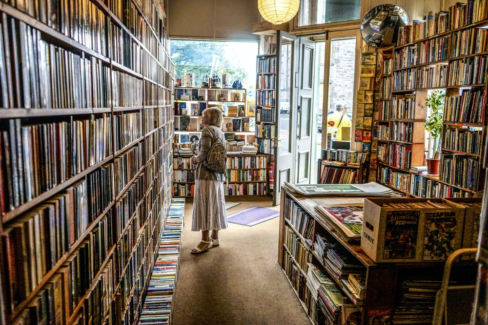 woman inside library looking at books