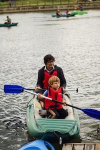 man and boy on raft paddling