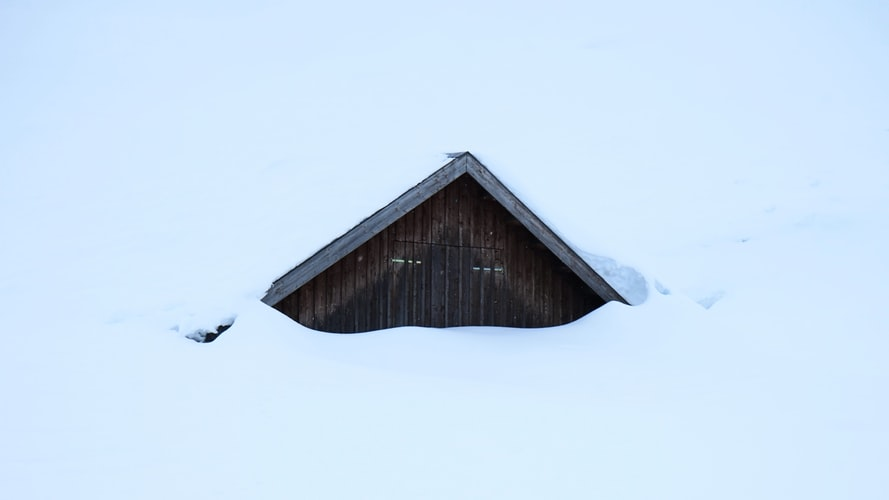 A photo of a cabin covered in snow - all you can see is the small peaked top of the roof.