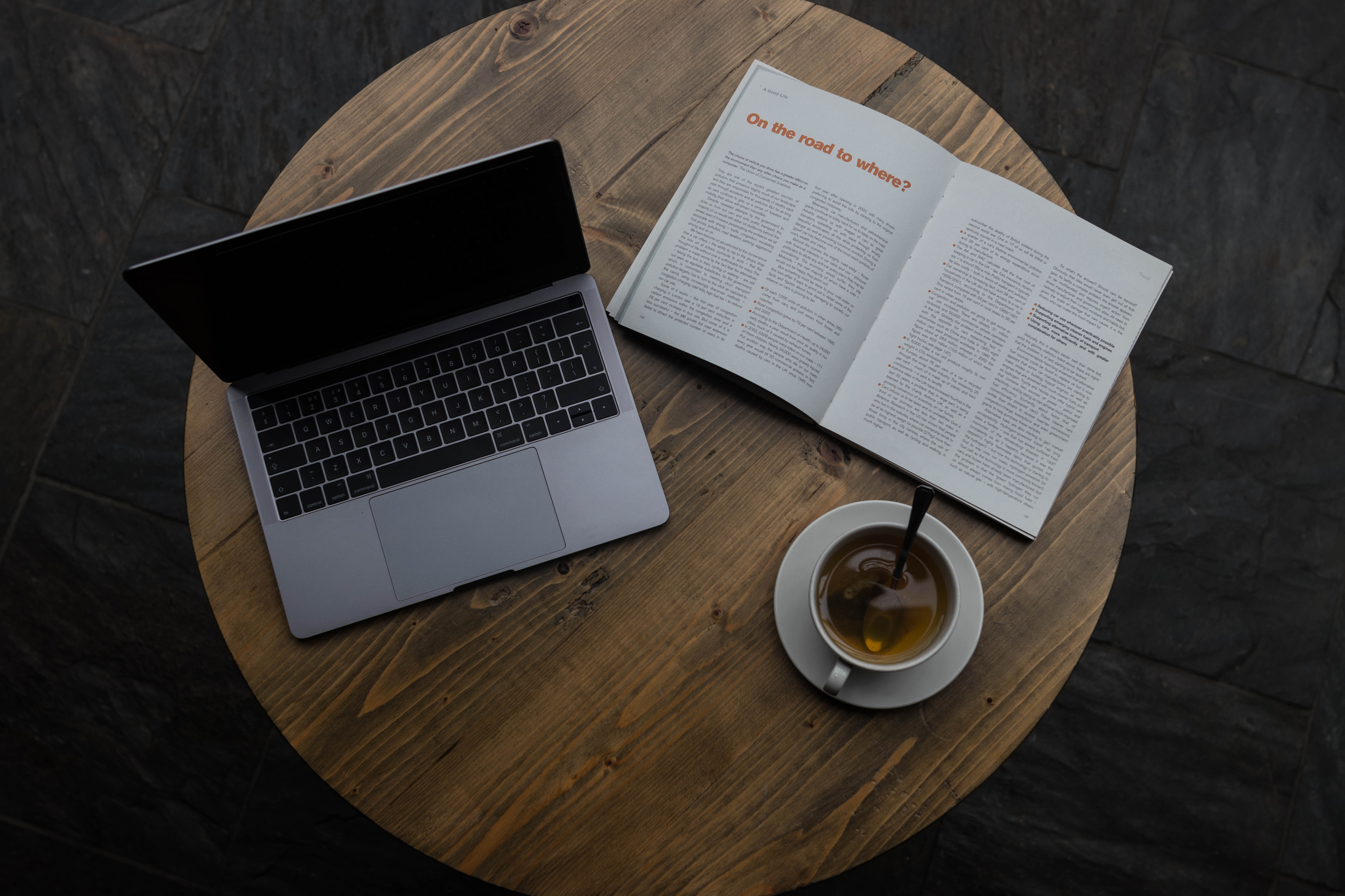 gray laptop beside white teacup and book