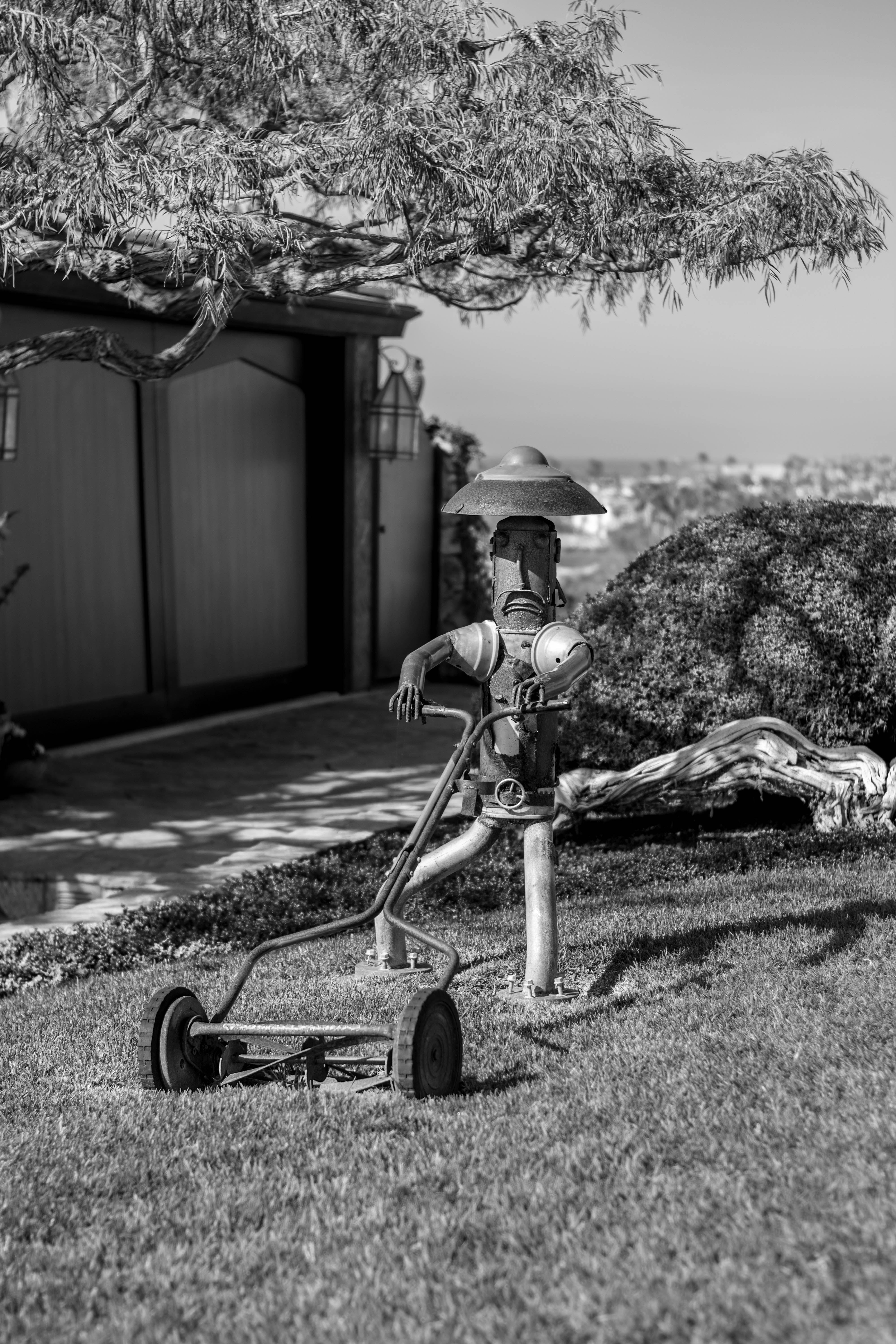 grayscale photography of robot man holding reel mower