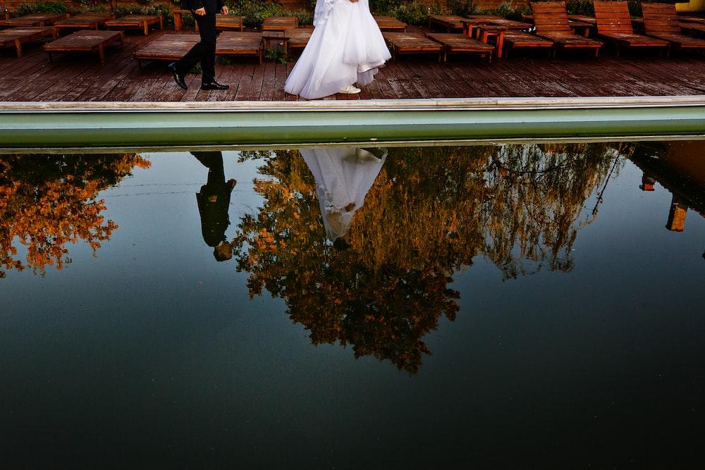 woman and man walking towards dock beside body of water