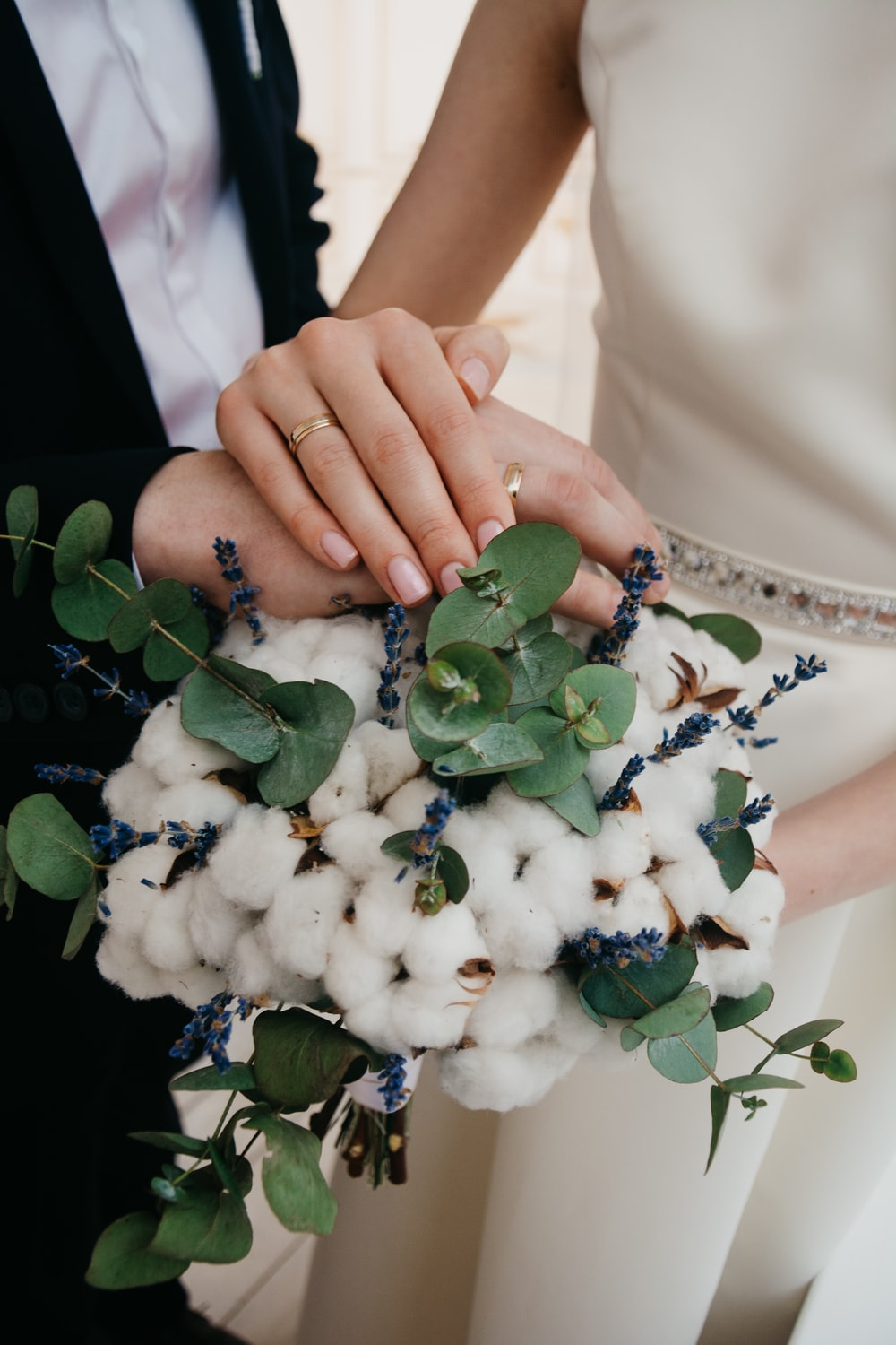 two person holding hands on white flower