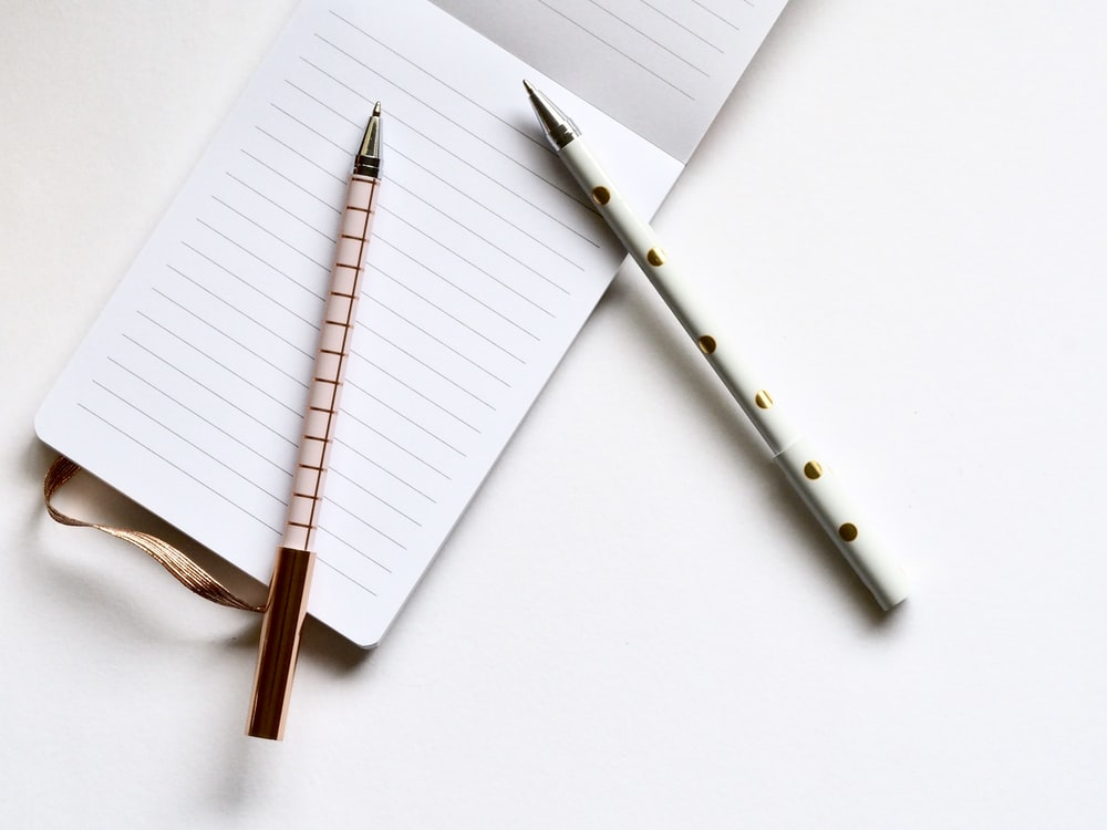 two white and beige pens on white paper