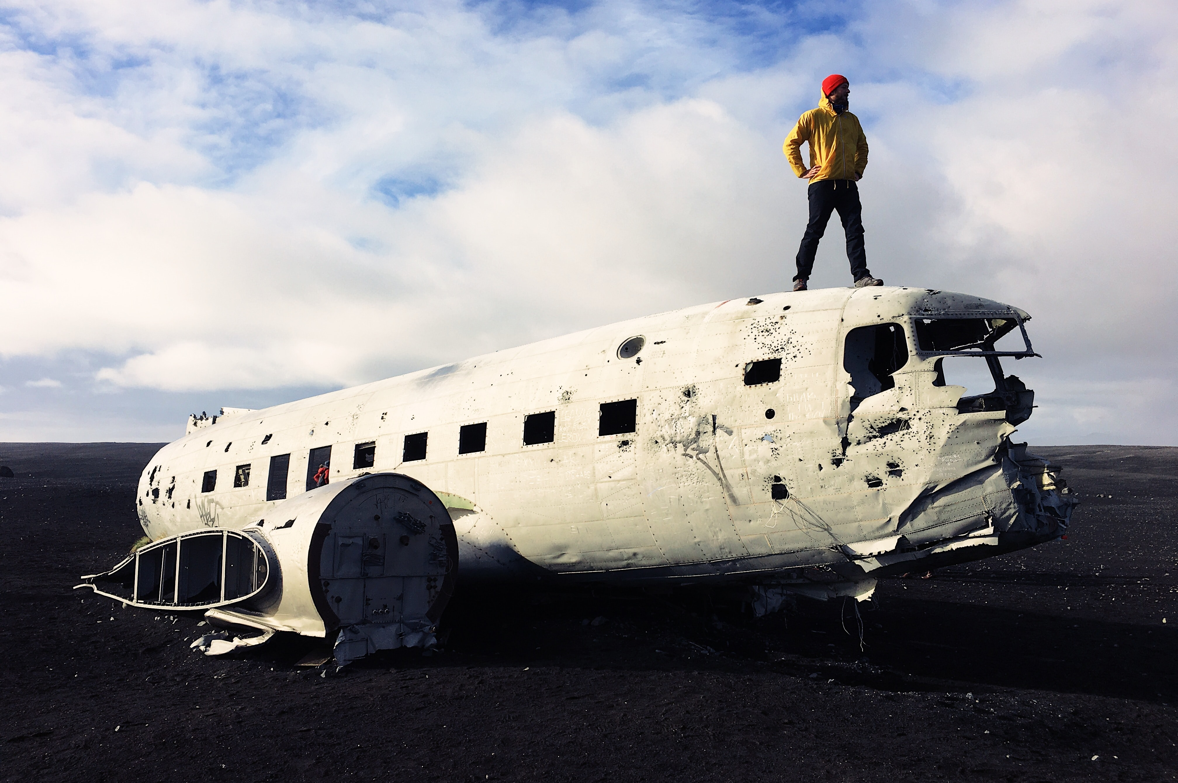 man standing on white abandoned plane under white sky
