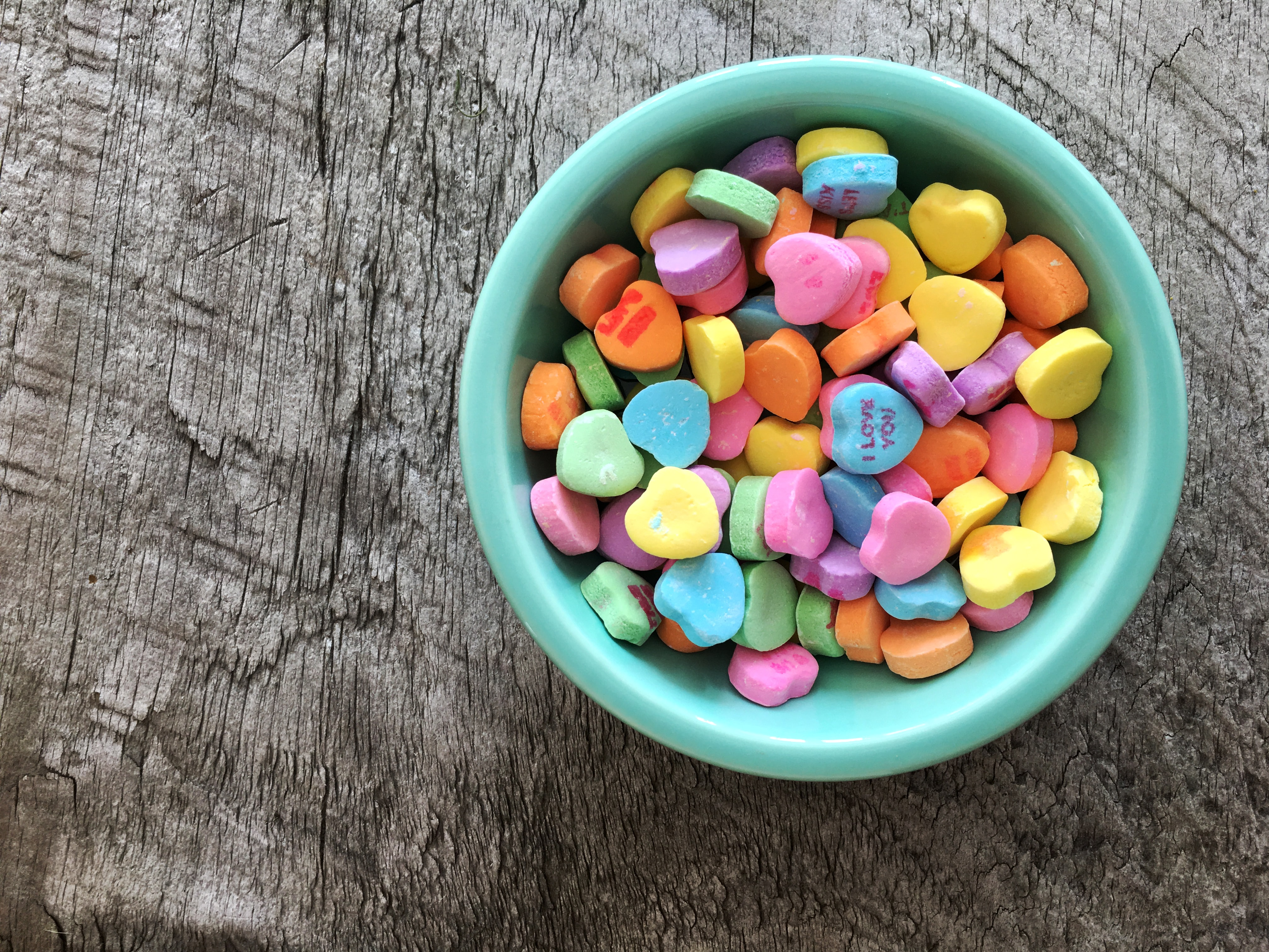 assorted-color heart shape candies on teal bowl