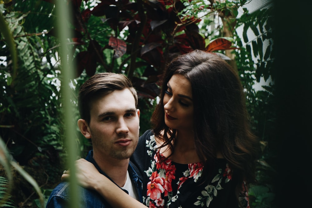man in blue top carrying woman in floral top