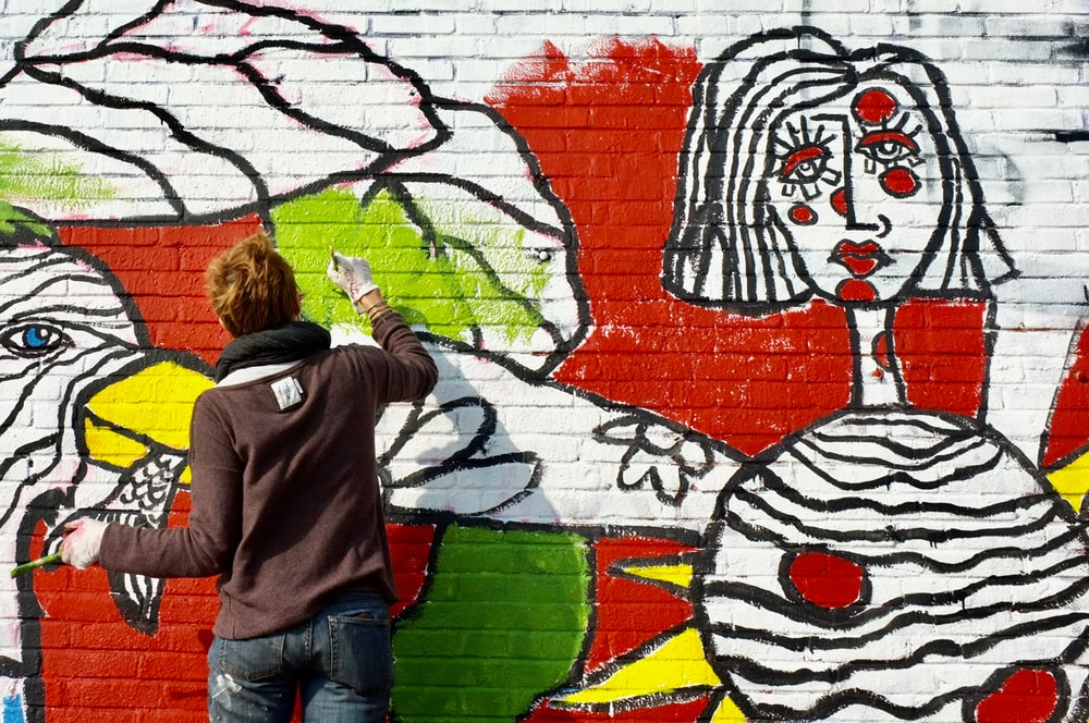 man painting on white wall during daytime