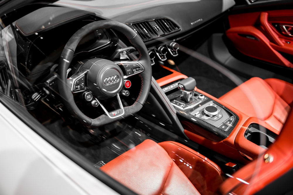closeup photography of red and black Audi vehicle interior