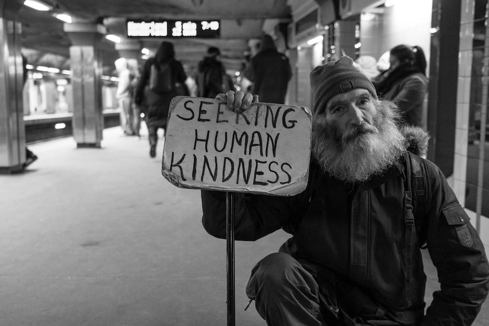 man holding card with seeking human kindness text