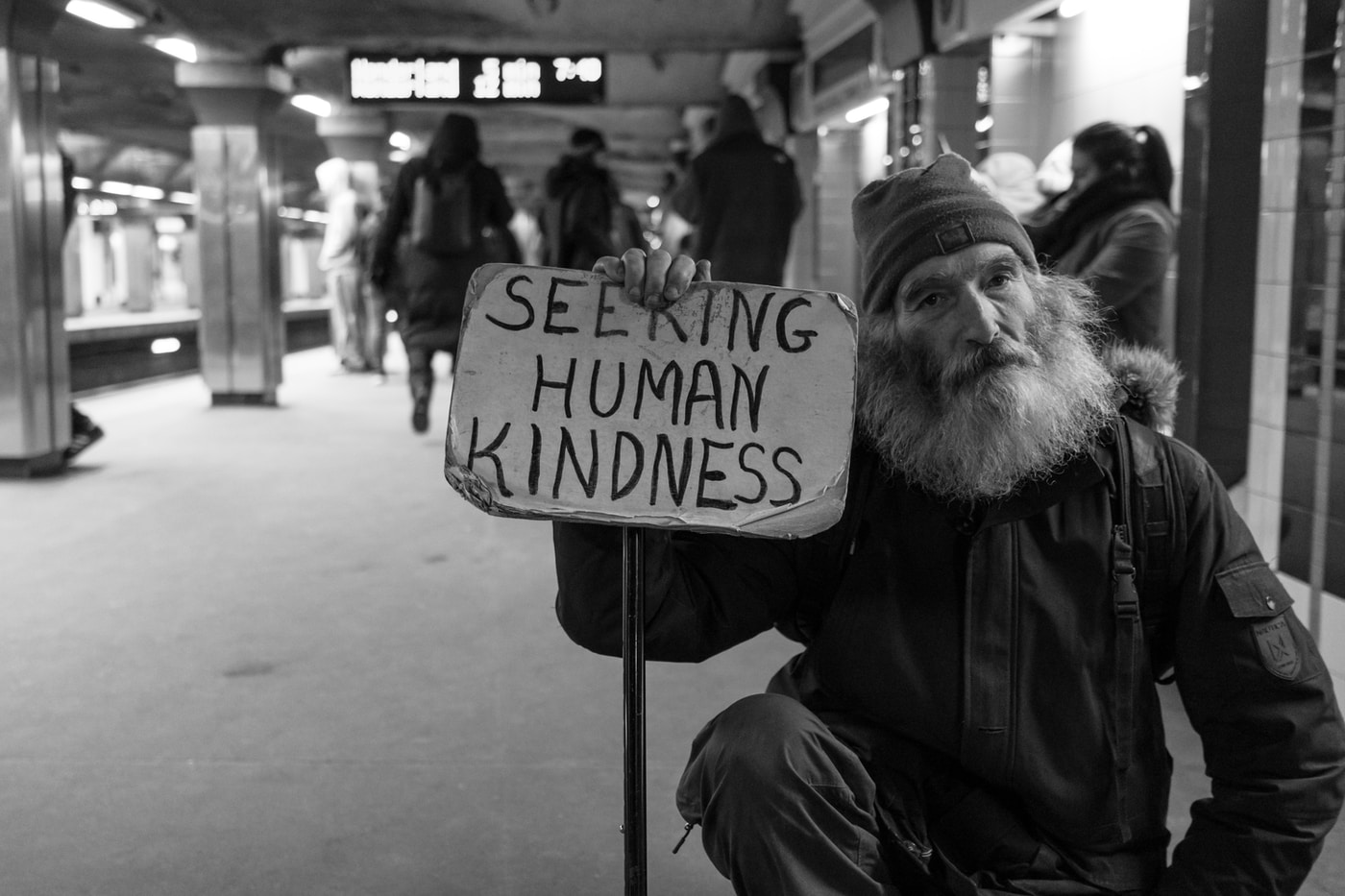 Help the homeless. man holding card with seeking human kindness text