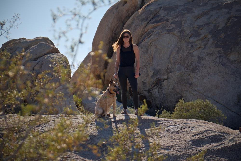 woman standing beside dog on rock