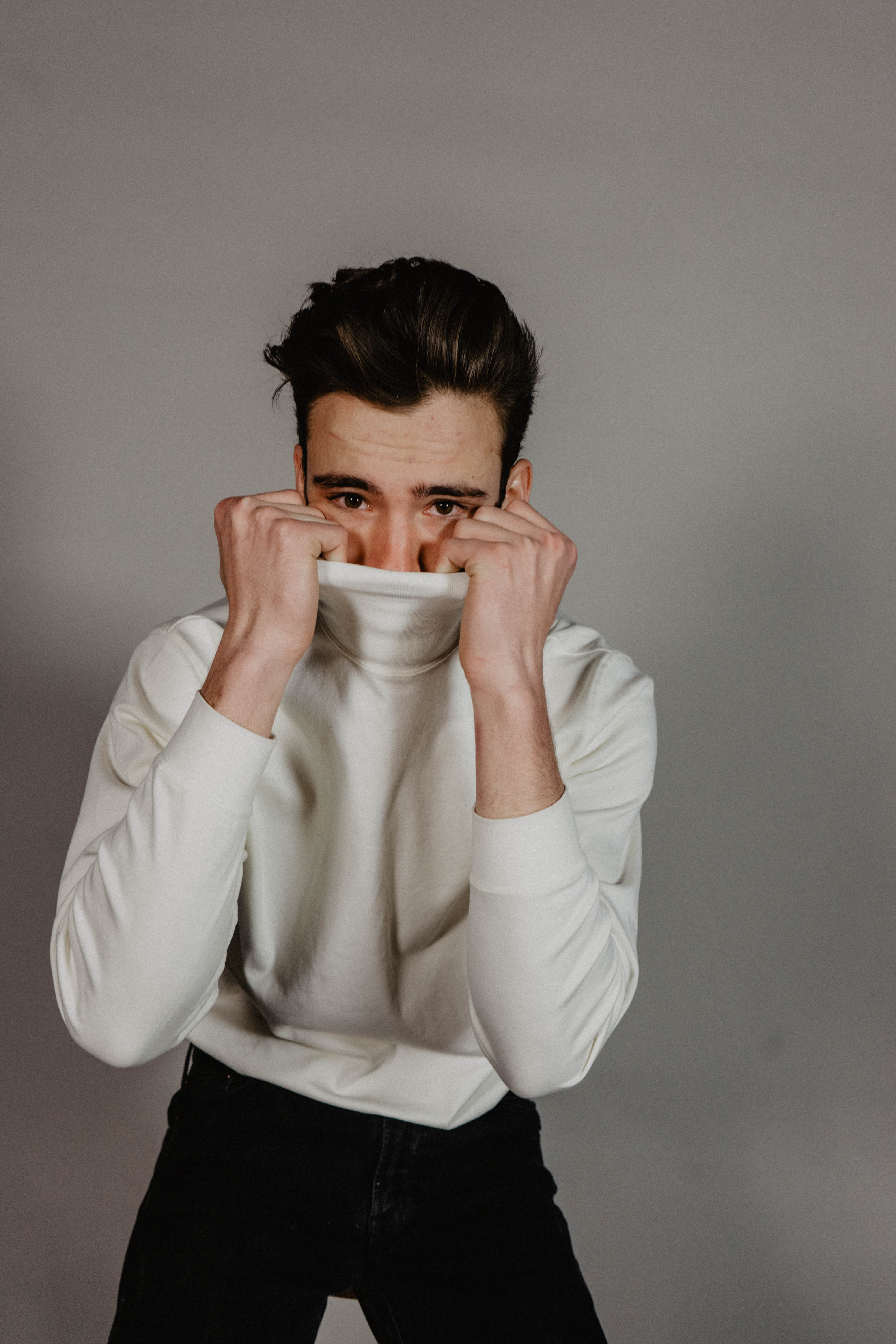 man covering his face with his sweater