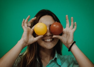 person holding yellow and red ball toys