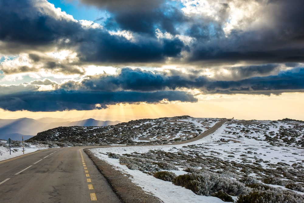 gray road in between snow covered field