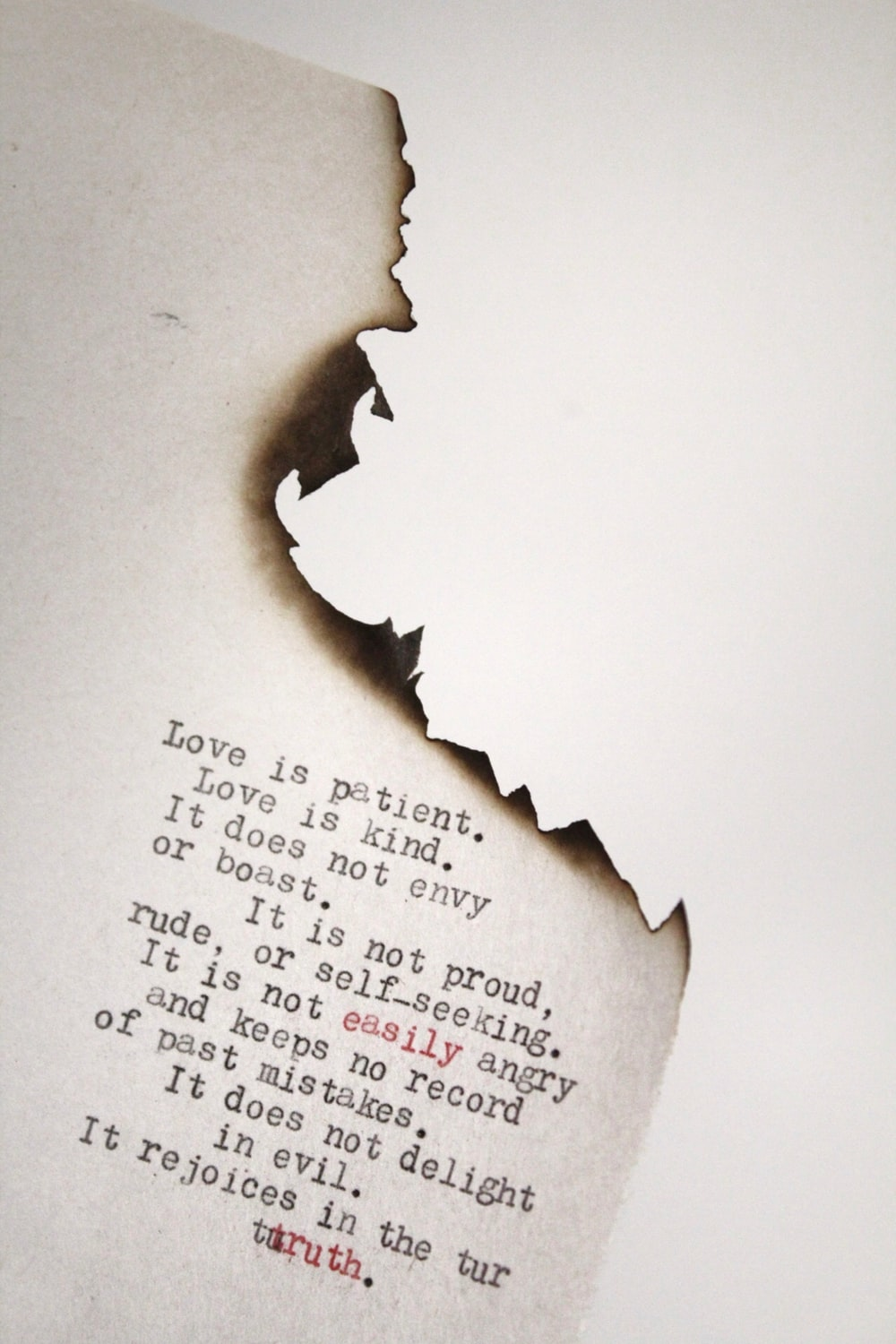 Love is patient Love is kind printed on burned paper