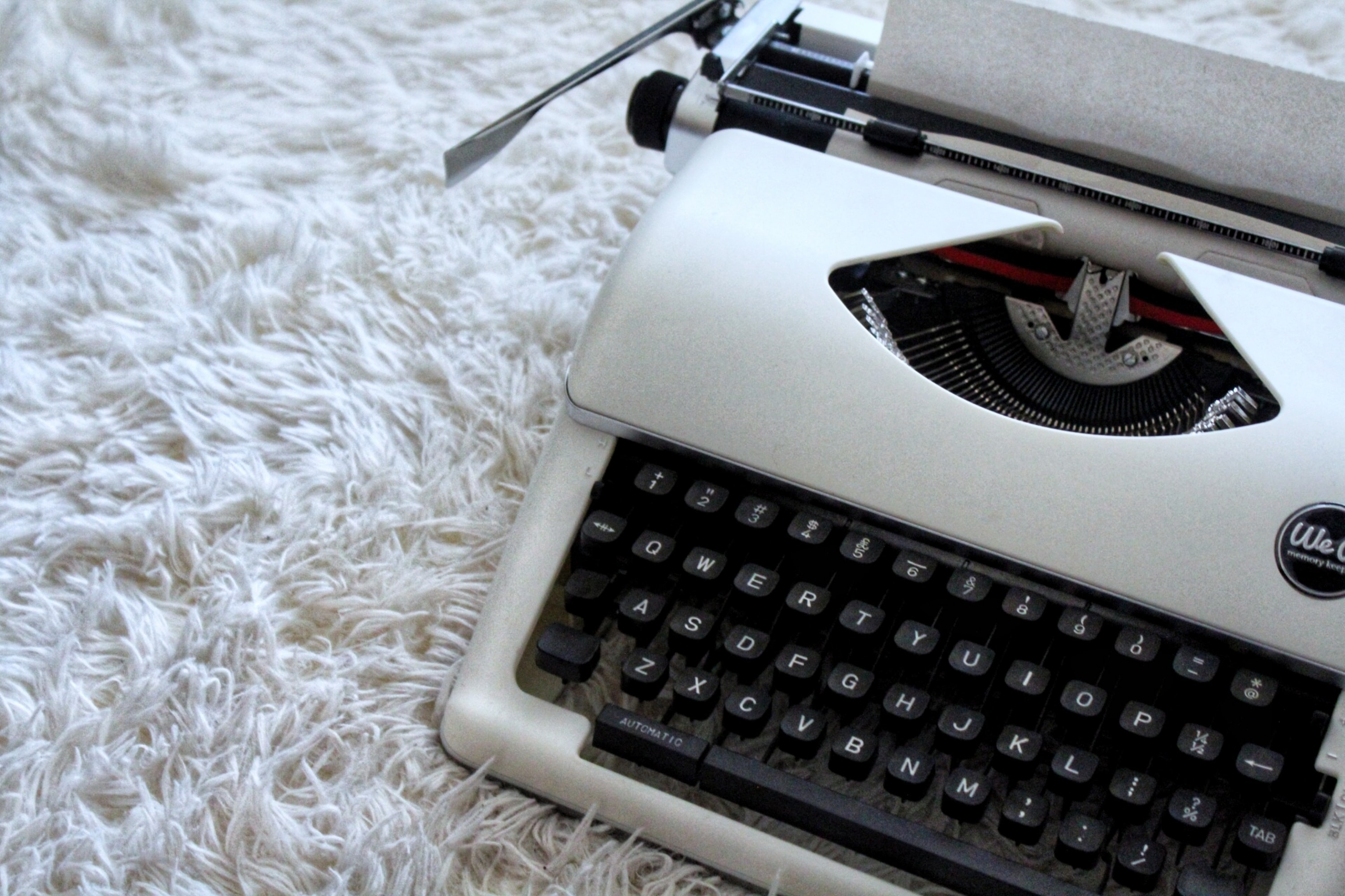 white and black typewriter on white textile
