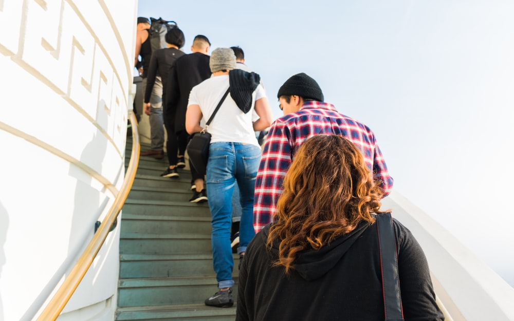 group of people on stairs under clear white sky