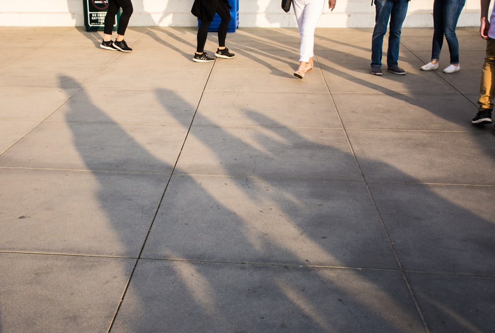 group of people standing on gray concrete tile flooring
