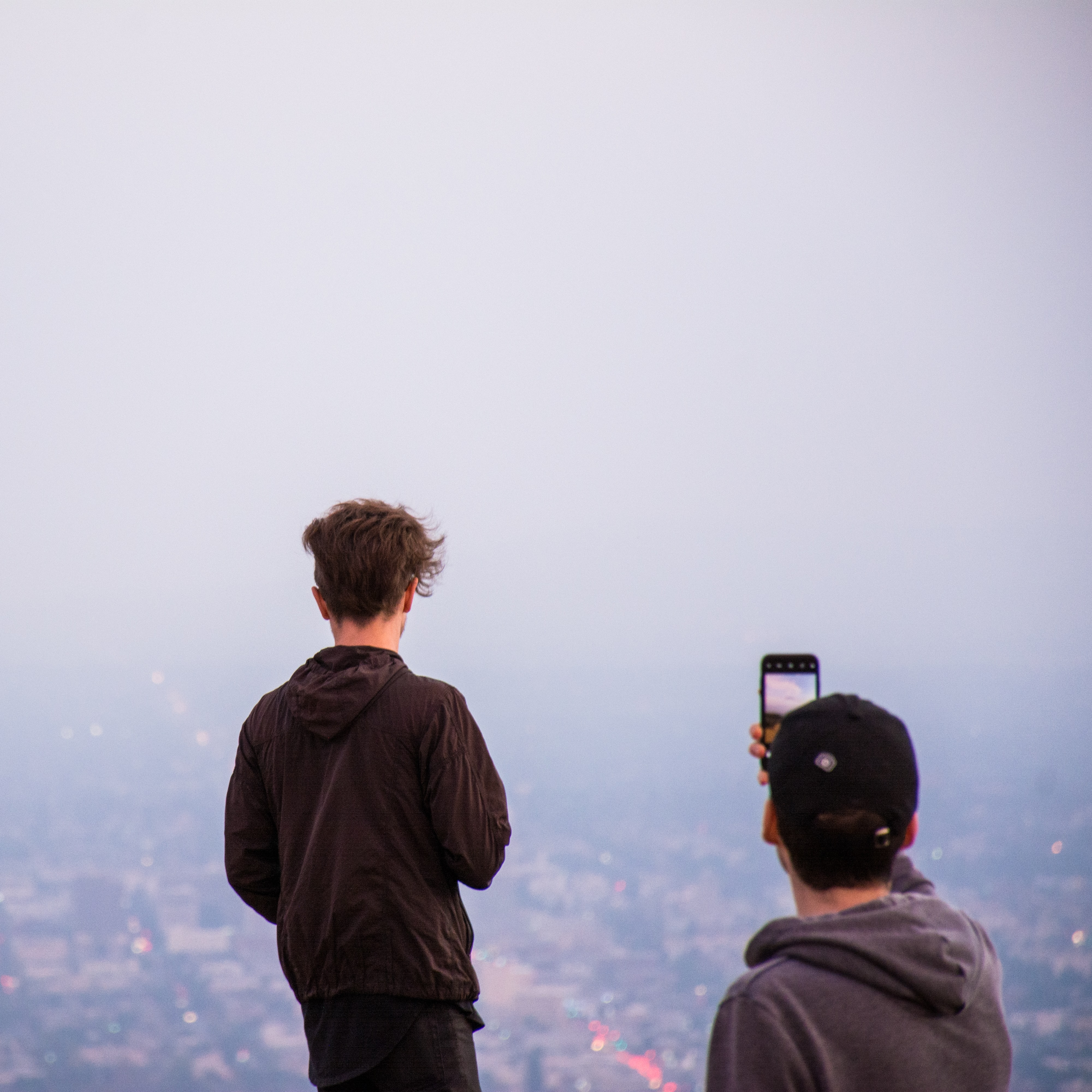 man taking a photo of a city during fog