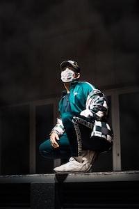 man wearing face mask crouching on wall