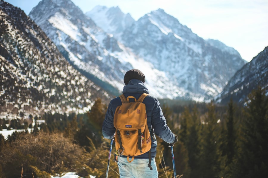 man wearing a backpack and standing on a mountain