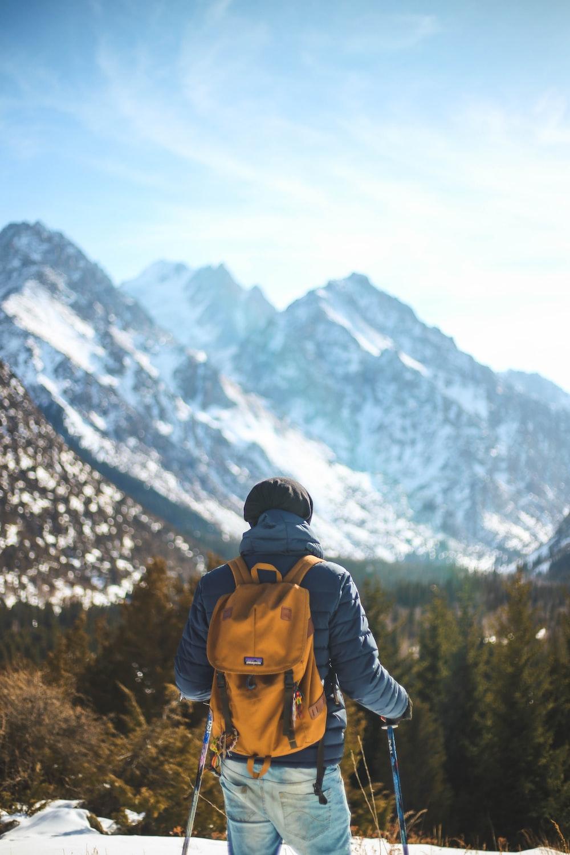man standing holding snow stick facing mountain