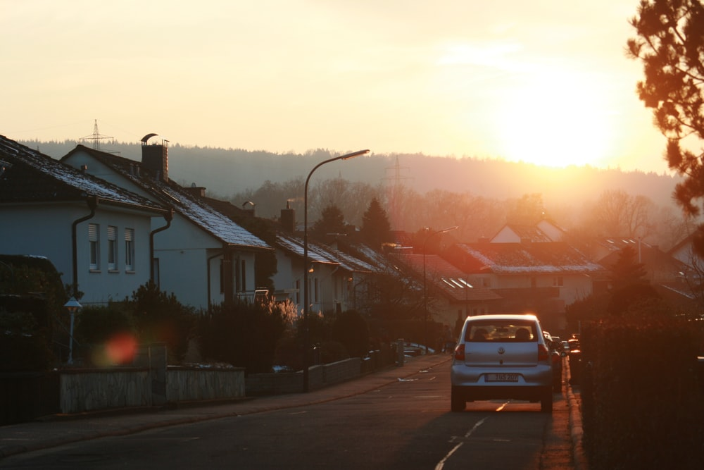 car passing through houses during golden hour