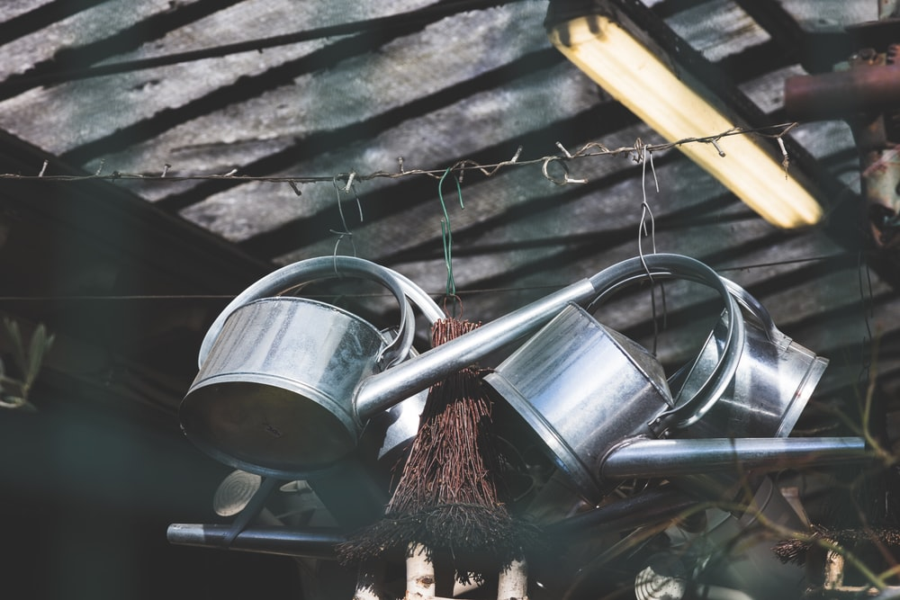 three hanged gray watering cans