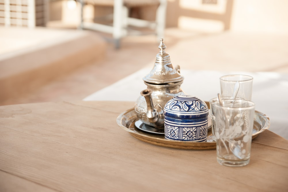 gray teapot set in tray place on brown table outdoors