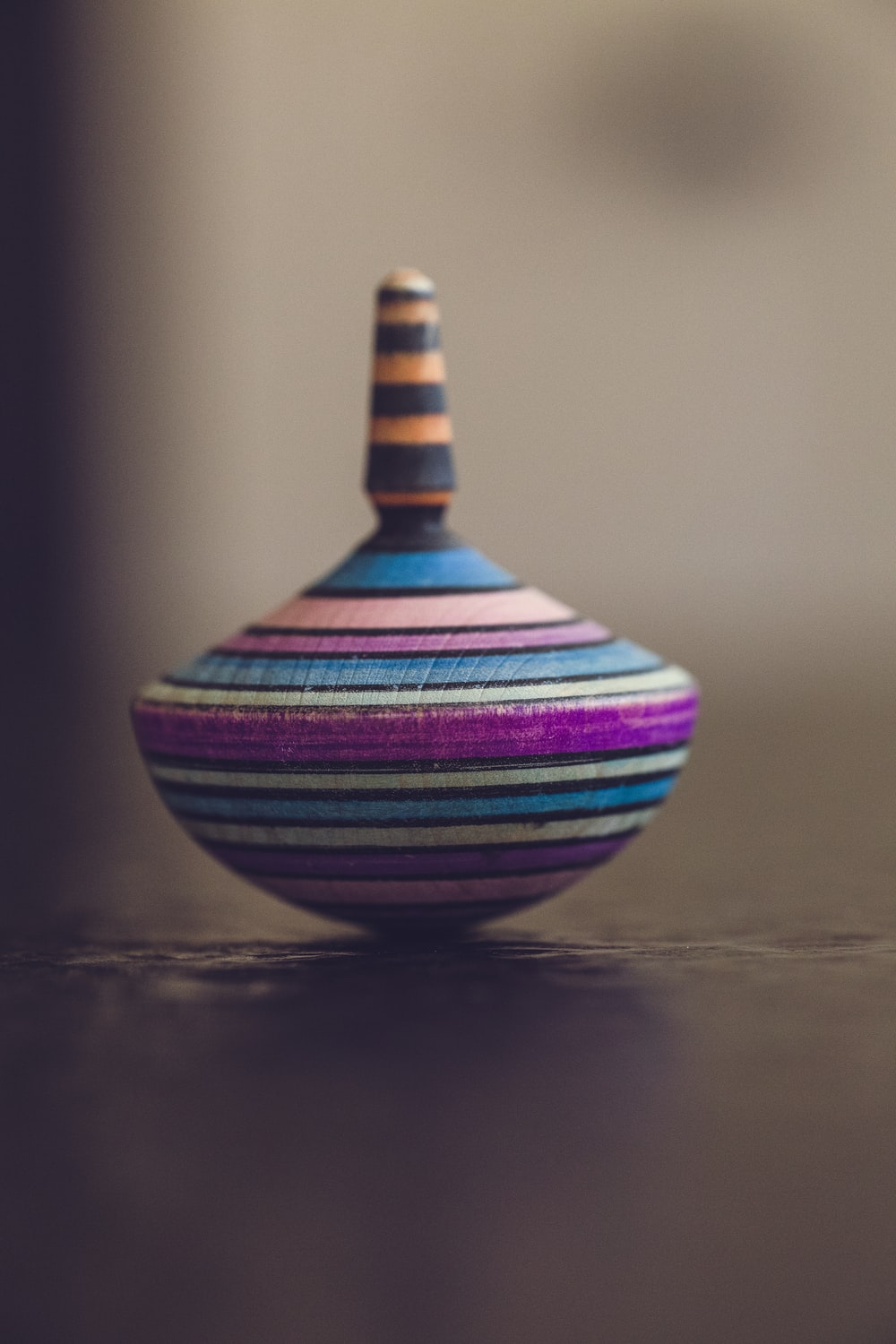 tilt-shift photography of multicolored spin top on brown surface