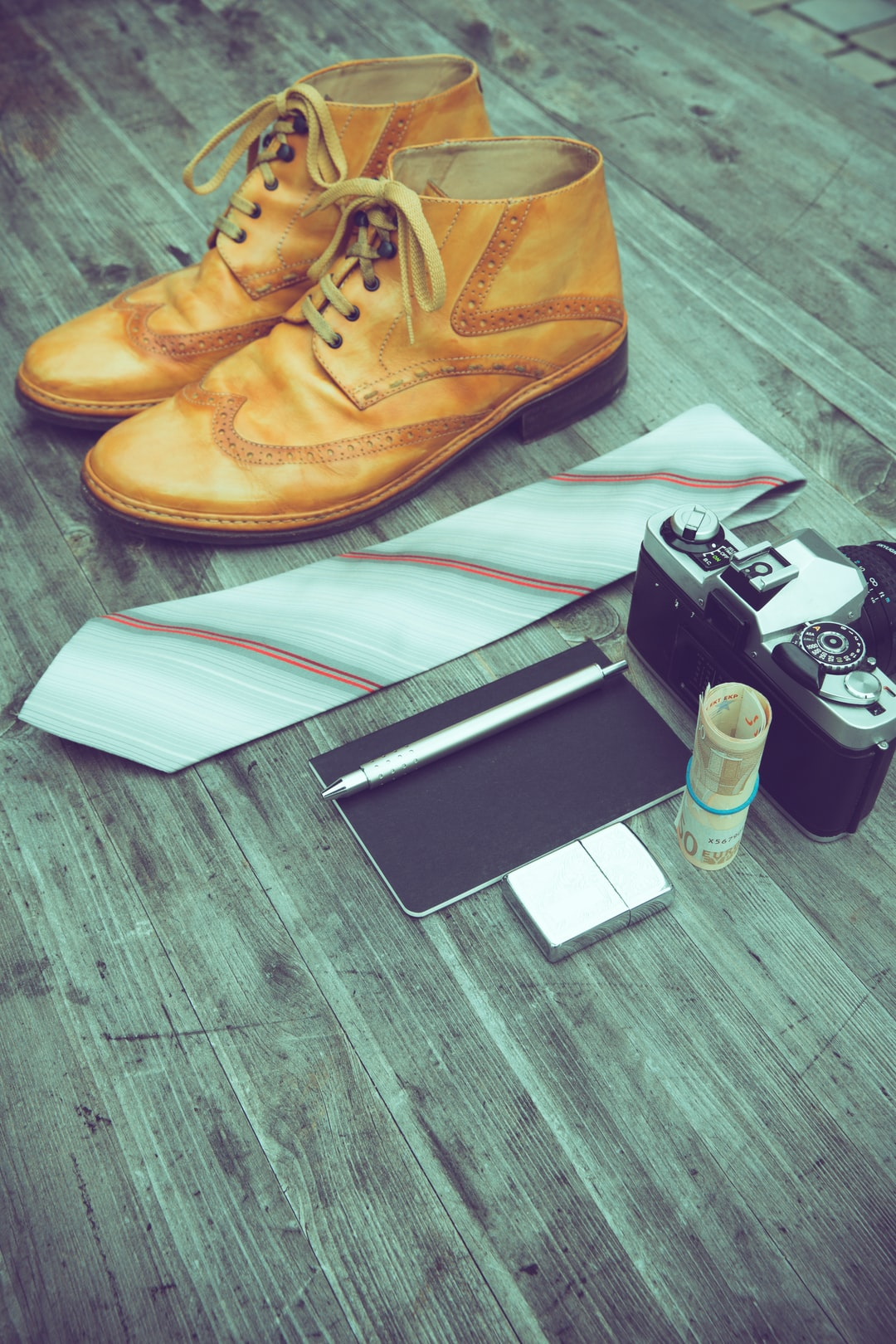 Handcraft italian leather laced boots, tie, vintage analog photo camera, notebook with silver pen, a roll of money and zippo fierstarter in flatlay.