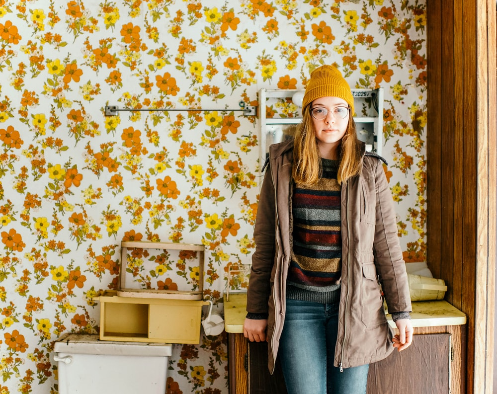 woman standing near cabinet in front of floral wallpaper