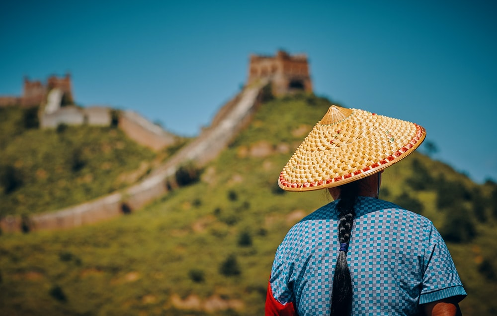 woman wearing hat facing The Great Wall of China